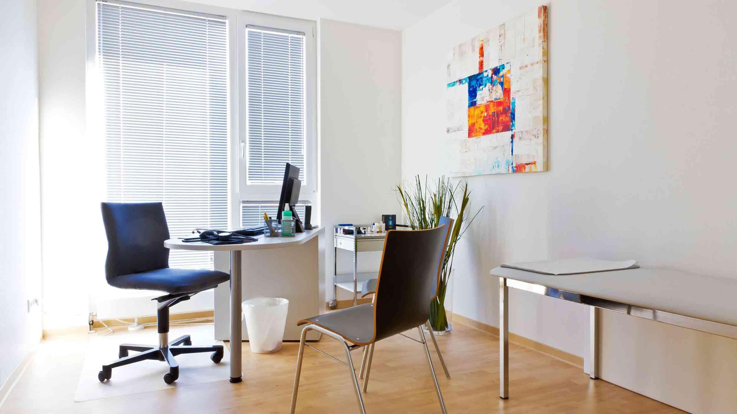 Schreibtisch mit Stühlen in Zimmer Hausarzt München