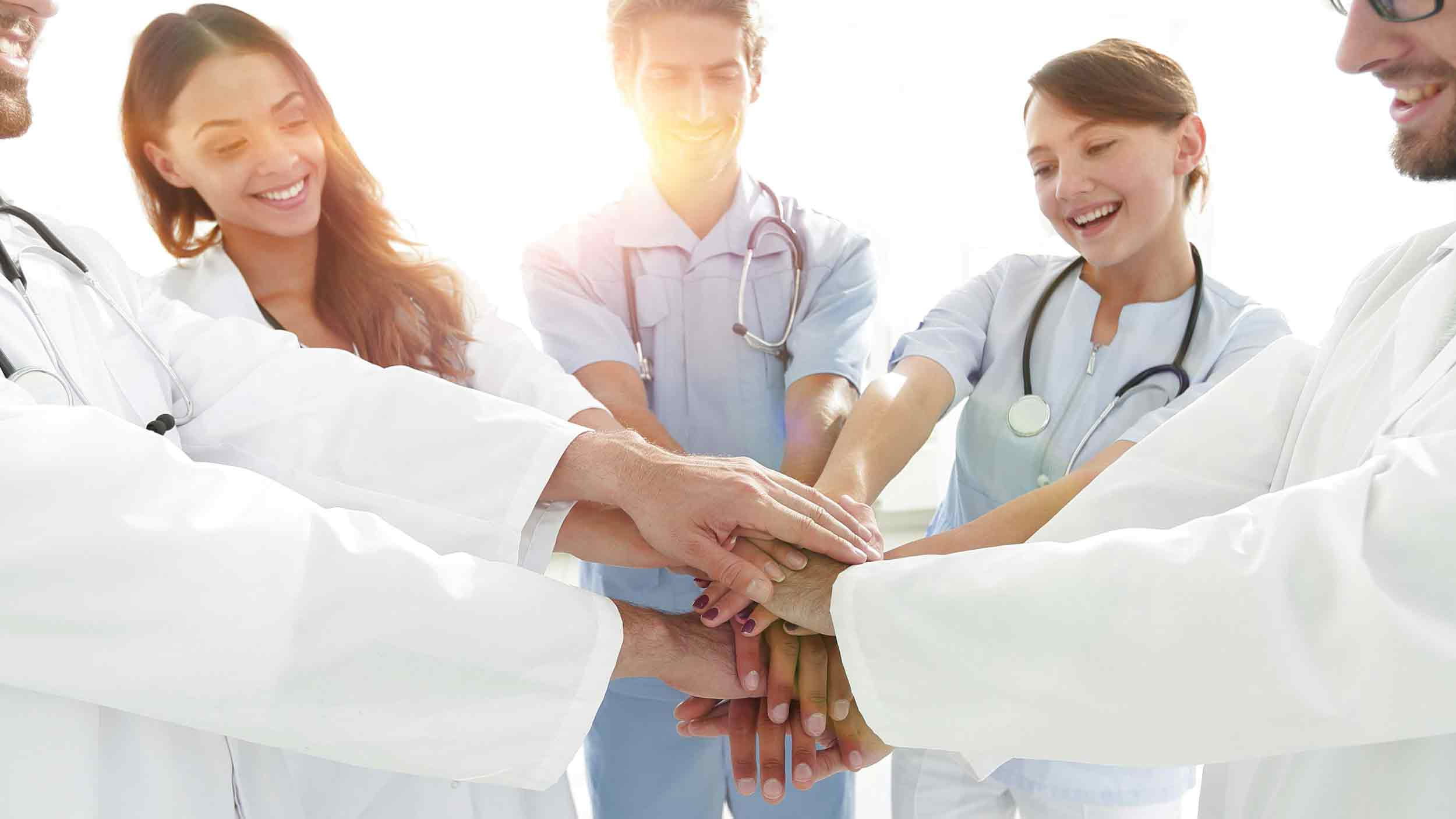 Ärzte und Personal stehen im Kreis legen Hände aufeinander
