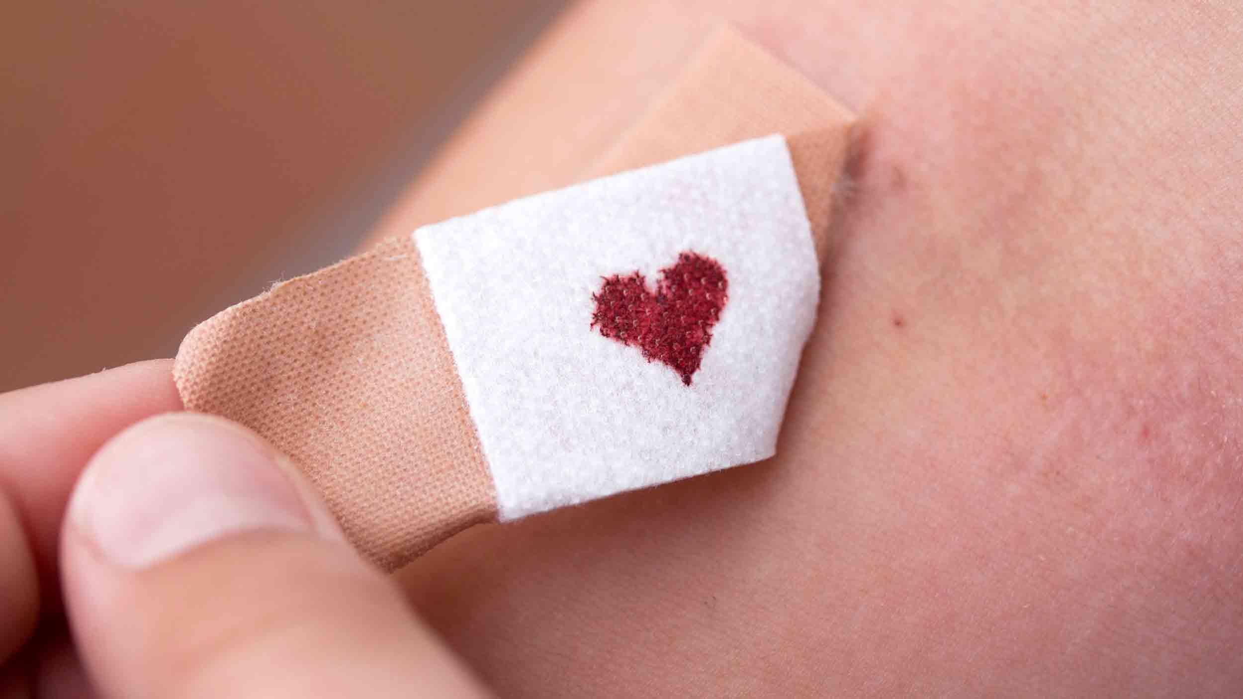 Pflaster Blutfleck Herzform wird abgezogen