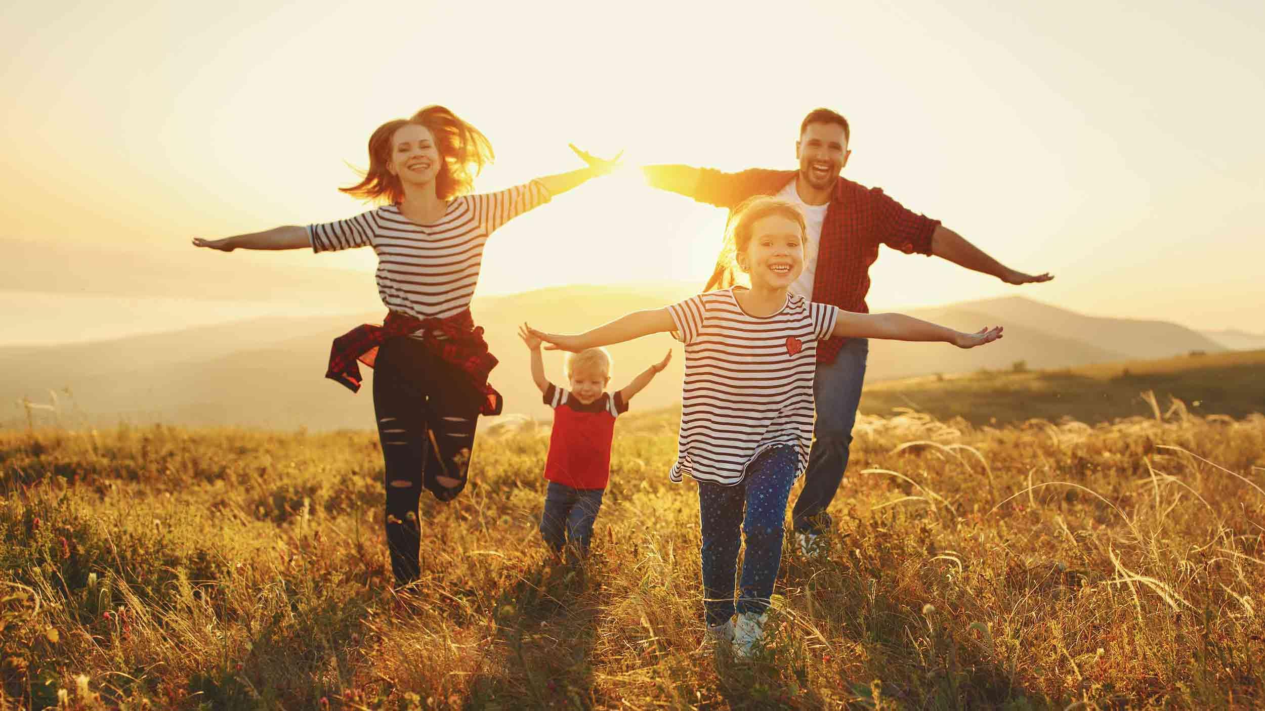 Paar mit zwei Kindern läuft bei Sonnenuntergang durch Wiese
