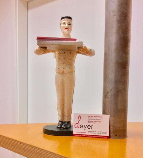 Dekofigur Arzt neben Visitenkarte Hausarztpraxis Dr. Geyer München