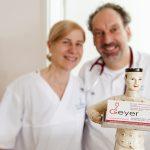 Drs. Geyer vor Figur mit Visitenkarte der Praxis Dr. Geyer